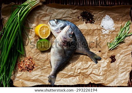 Two fresh Dorada laid out on brown paper for baking,Cook put on paper fresh fish to marinate it later - stock photo