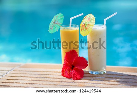 Two fresh fruit cocktails on wooden planks in front of a blue swimming pool - stock photo