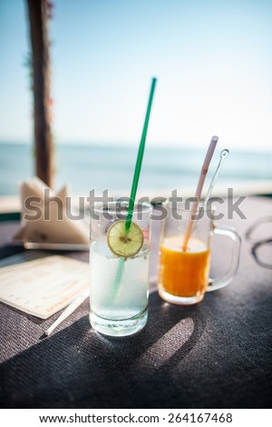 Two fresh juices cocktails close-up on the table on the beach near the sea ocean - stock photo