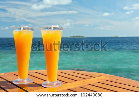 Two fresh juices cocktails orange on the table near the sea. - stock photo