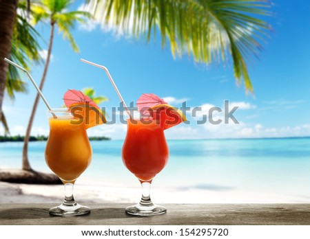 Two fresh juices on beach - stock photo