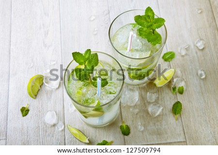 Two fresh mojitos cocktail. Mojitos with mint leaves, lime and ice - stock photo