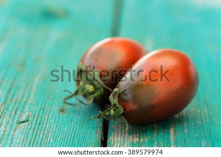 Two fresh organic red and black tomatoes on old wooden turquoise table copyspace - stock photo
