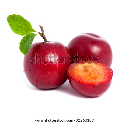 Two fresh plums and a half with leafs isolated on white background