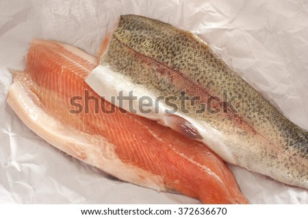 Two fresh rainbow trout fillets, one flesh side up and one skin side up, on greaseproof paper ready to be cooked for a healthy seafood dinner - stock photo