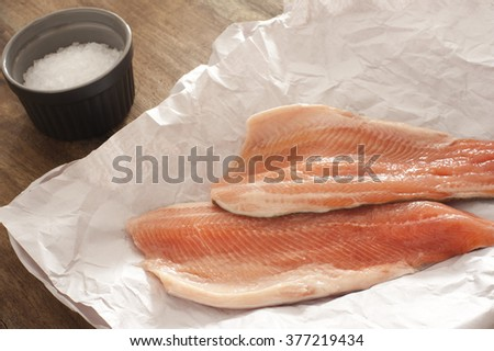 Two fresh raw rainbow trout fillets on crumpled white paper for a delicious seafood dinner with a small dish of coarse salt alongside - stock photo