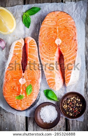 Two fresh raw salmon steaks on paper with salt, peppers, lemon, and basil on the rustic wooden table - stock photo