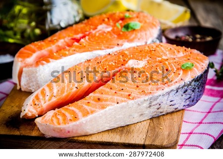 Two fresh raw salmon steaks with peppers on wooden cutting board - stock photo