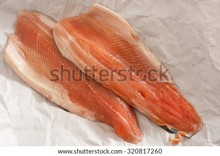 Two fresh raw trout fillets laid out on crumpled white paper ready to be cooked for a gourmet seafood meal - stock photo