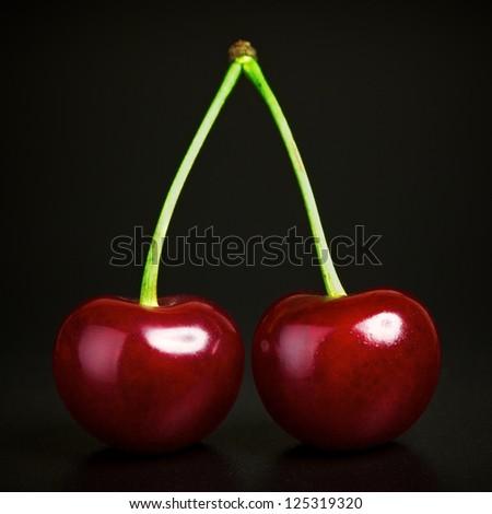 two fresh ruby cherries on black background - stock photo