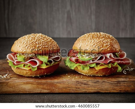 two fresh sandwiches on wooden cutting board