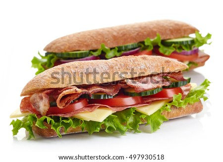 Two fresh submarine sandwiches with ham, cheese, bacon, tomatoes, lettuce, cucumbers and onions isolated on white background