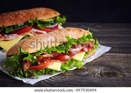 Two fresh submarine sandwiches with ham, cheese, bacon, tomatoes, lettuce, cucumbers and onions on dark wooden background