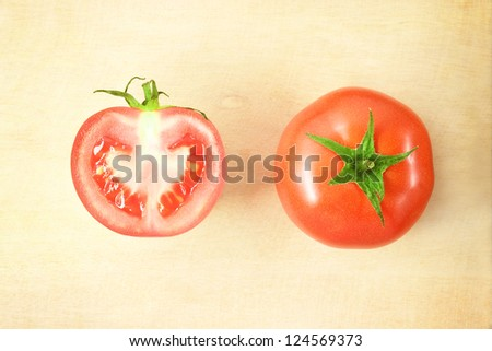 two fresh tomatoes on wooden cutting board