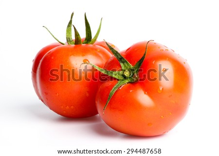 Two fresh tomatoes with green leaves isolated on white background. - stock photo