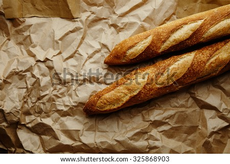 Two freshly baked baguettes in corner on craft paper