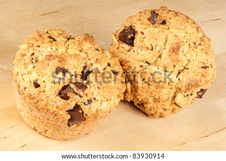 Two freshly baked homemade chocolate chips muffins over a wooden background