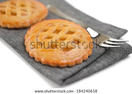 Two freshly baked homemade tarts on a grey napkin