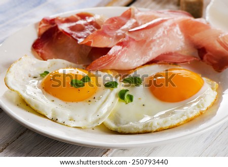 Two fried eggs and bacon for healthy breakfast . selective focus - stock photo