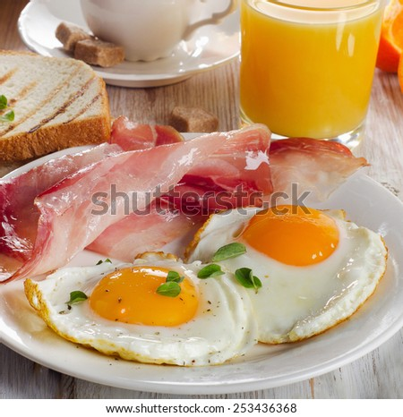 Two fried eggs, bacon,toasts, juice and coffee.Selective focus