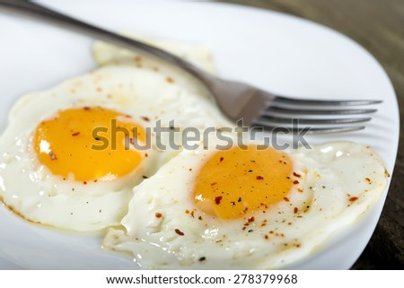 Two fried eggs for healthy breakfast in white plate - stock photo