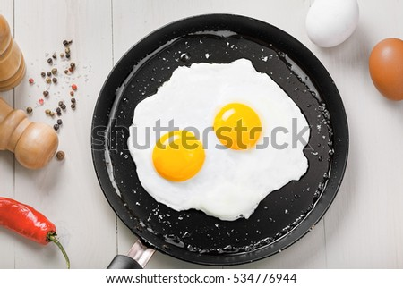 Two fried eggs in a frying pan cooked for breakfast. Delicious international meal on a table. Homemade food, top view.