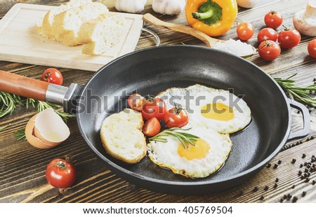 two fried eggs in a frying pan on a wooden table on a background of greens and vegetables - stock photo