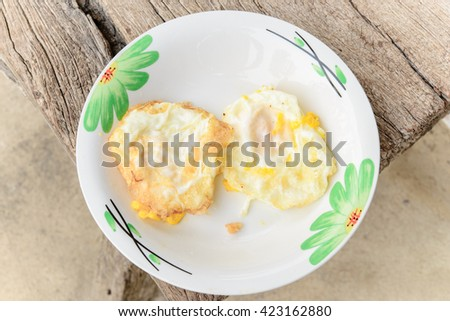 Two fried eggs in plate on wood chair - stock photo