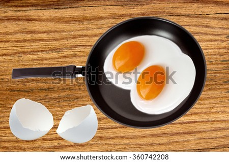 Two fried eggs on a pan on wooden table background - stock photo
