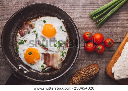 Two fried eggs with bacon and onion, tomato and bread on the side - stock photo