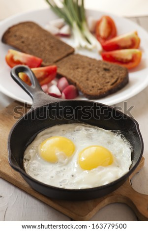 Two fried eggs with yellow yolks and vegetables - stock photo