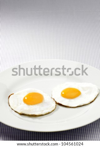 Two fried eggs with yellow yolks on white plate with gingham tablecloth - stock photo