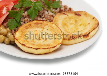 Two fried pieces of vegetable marrows and buckwheat cereal with tomatoes and parsley - stock photo