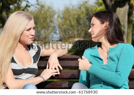 Two friended woman at park talking - stock photo