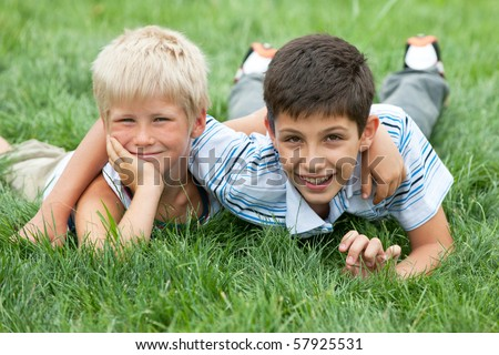 Two friendly boys are lying on the green grass