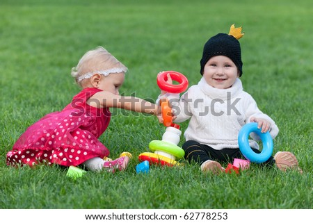 Two friendly little girls are playing with bright toys on the green grass
