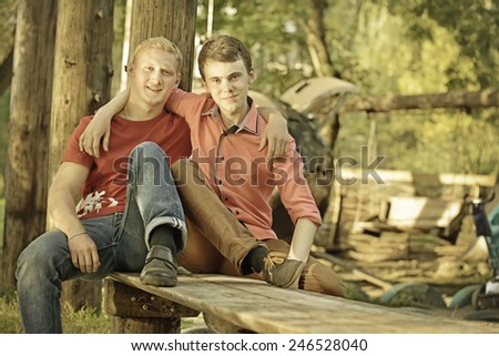 Two friendly male mature students outdoors in park sitting on bench. Two guys hugging - stock photo