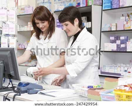 Two Friendly Pharmacists Working Together in the Drugstore . - stock photo