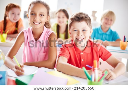 Two friendly schoolkids looking at camera at lesson