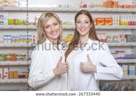 Two friendly smiling pharmacists show thumbs up in pharmacy environment - stock photo