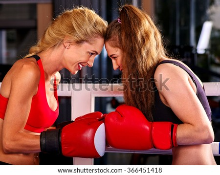 Two  friendly women boxer wearing red  gloves to box in ring. - stock photo