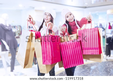 Two friends are shopping in winter time at the mall - stock photo