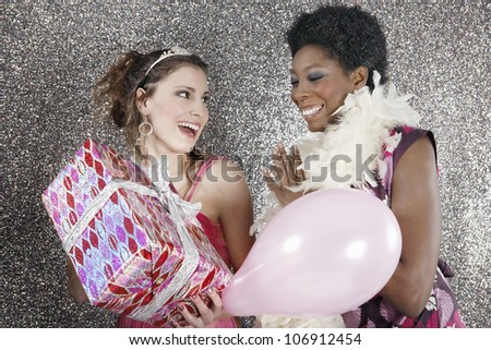 Two friends at a birthday party with gifts and balloons, smiling.