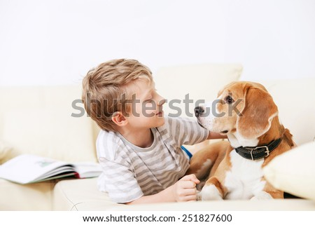 Two friends - boy and dog lying together on sofa - stock photo