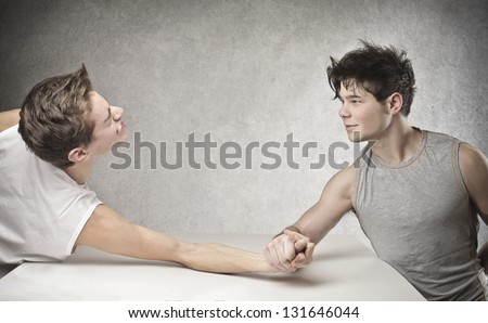 two friends challenge each other at arm wrestling - stock photo