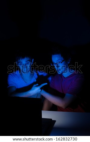 Two friends chatting on a laptop with webcam - stock photo