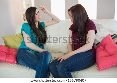 Two friends chatting on the sofa at home in living room