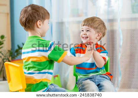two friends children boys play together indoors - stock photo
