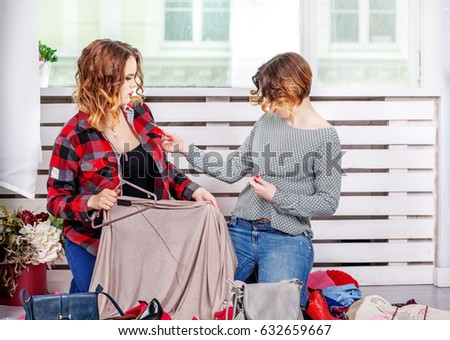 Two friends choosing clothes of her wardrobe. The concept of fashion, style, friendship.
