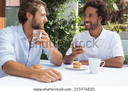 Two friends enjoying coffee together outside at the coffee shop - stock photo